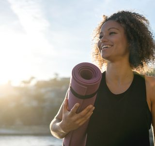 Portrait of a fit woman holding a yoga mat at the beach and looking very happy - wellness concepts