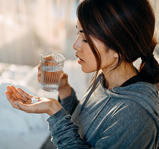 Young Asian woman sitting on bed and feeling sick, taking medicines in hand with a glass of water